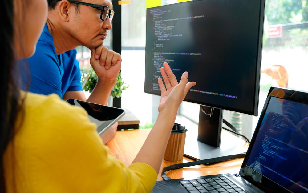 Um homem e uma mulher analisando dados